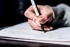 Hand mit Bleistift beim Schreiben